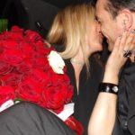 Coppia si bacia durante un felice anniversario festeggiato con sorpresa di rose rosse e limousine