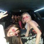 Ragazze a bordo della limousine festeggiano sorridenti