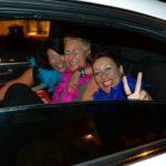 Donne con boa di struzzo colorati festeggiano divertite nella limousine