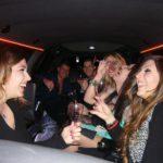 Ragazze e ragazzi si divertono sorseggiando prosecco in limousine
