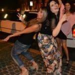 Ragazze con bicchieri di prosecco in mano si divertono al Colosseo vicino limousine